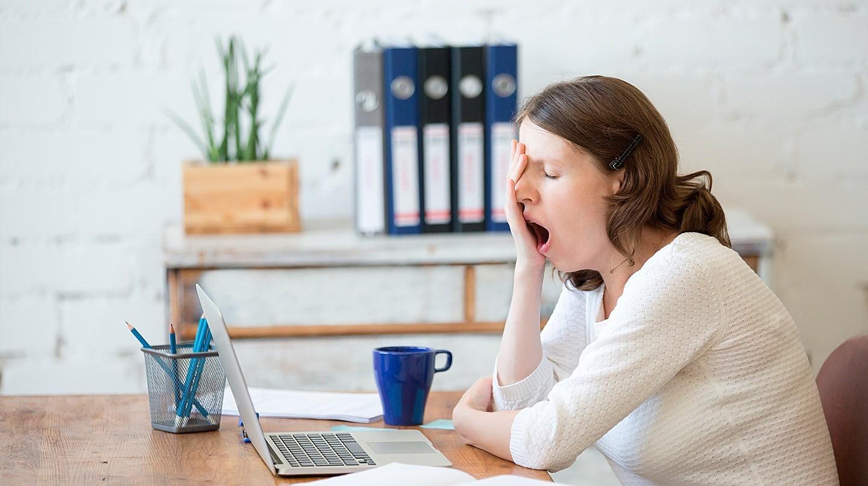 Eine Frau sitzt im Büro vor dem Laptop und gähnt.