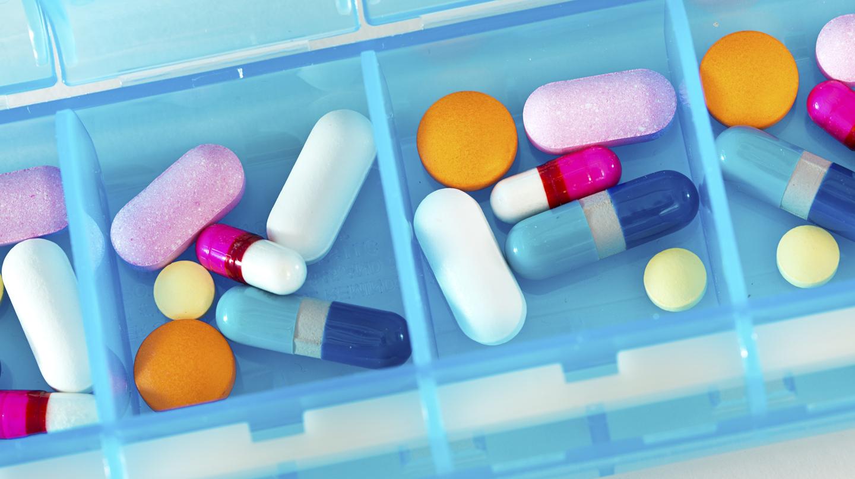 Medikamente einnehmen: Bunte Mischung von Tabletten und Kapseln und einer hellblauen Tablettenbox.